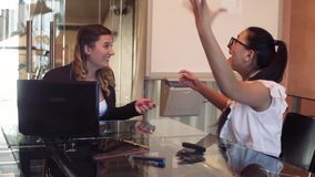 Two business women in business clothes are happy throwing documents and clapping hands after one of them reported good. Two young beautiful business women in stock video