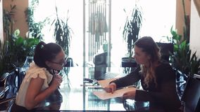 Two business women discussing a business project while sitting at a table in the office opposite each other using a. Two business women in business clothes stock video footage