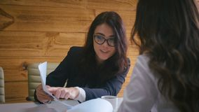 Two business women colleagues sitting at conference table discussing a new project business plan at modern office stock video footage