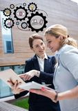 Two business women with devices and black gear graphics Royalty Free Stock Photo