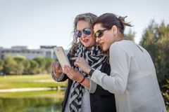 Two business women discuss something important they are reading on a tablet. Two businesswomen in casual clothes comment on something important they are reading stock images