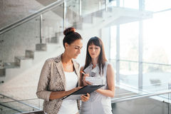 Two business women discussing checklist Stock Photography
