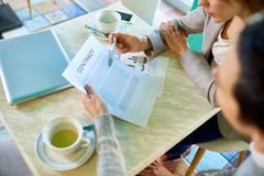 Two Business Women Discussing Contract. Portrait of two unrecognizable businesswomen reading contract sitting at table in modern office and negotiating deal Stock Photos
