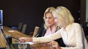 Two business women are discussing for a laptop their new working project. Two blondes are sitting behind a laptop. She is looking at that in the laptop. Girls stock video