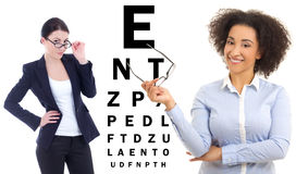 Two business women in glasses and eye test chart isolated on whi Royalty Free Stock Images