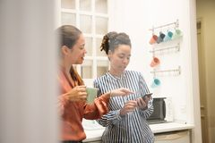 Two woman pointing at a cell phone in a kitchen royalty free stock photo