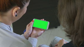Two business women holding a smartphone with green screen. 4k stock footage