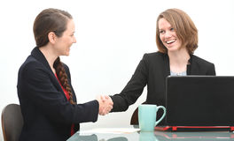 Two business women in interview or negotiation shaking hands Royalty Free Stock Image