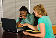 Two business women look at a laptop computer. In an office conference room. One of the women yawns as if tired or bored with the work Stock Image