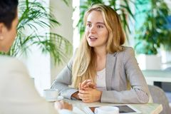 Two Business Women Meeting in Cafe. Portrait of two modern young women discussing work sitting at table in cafe during business meeting, focus on young blond Royalty Free Stock Photos