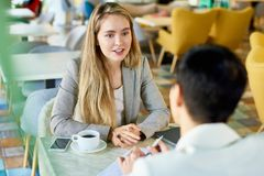 Two Business Women Meeting at Cafe Table. Portrait of two modern young women discussing work sitting at table in cafe during business meeting or job interview Stock Images