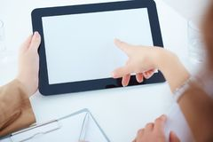 Tablet blank screen for promotional messages. Two business women in a meeting discussing information on a tablet-pc. Two business women in a meeting discussing stock photography