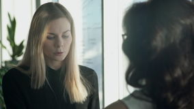 Two business women next to window in hall discuss topics. Tall blonde woman with straight hair in black shirt speaking to employee, says important ideas in stock video