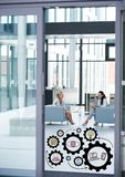 Two business women in office with black gear graphics Stock Photos