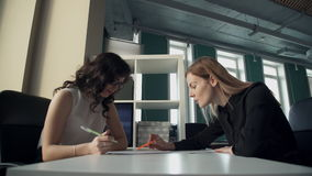 Two business women in office discuss topics, watching documents. Blonde woman with straight hair, black shirt sits with paper, pen, speaking to employee stock video