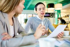 Two Business Women Reading Documents in Cafe. Portrait of two modern businesswomen reading documents sitting at table in cafe and  discussing work, focus on Stock Photo
