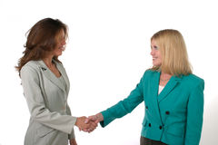 Two Business Women Shaking Hands 1. Attractive and beautiful two business woman team smiling and shaking hands. Shot on white Stock Photo