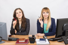 Two business women sitting at a desk, holding pen in hand and look to the Frame Royalty Free Stock Image