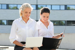 Two business women sitting with laptop and folder over street ba Royalty Free Stock Photos