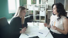 Two business women sitting at table in office discuss topics. Tall blonde woman with straight hair, black shirt sits with paper, pen, listening to employee stock video footage