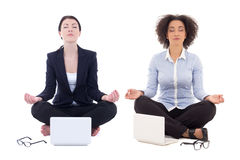 Two business women sitting in yoga pose with laptops isolated on Royalty Free Stock Photos