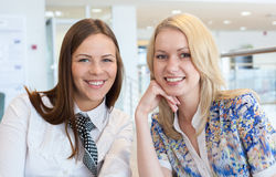 Two business women smiling. In car service Stock Photos
