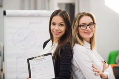 Two business women standing at office in front of flip chart Stock Photography