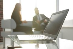 Focus on laptop on the table. Blurred people on background. Royalty Free Stock Image