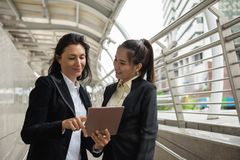 Two business women with tablet in city. Senior American female business manager point finger to digital tablet to check business project plan with her Asian Stock Photography
