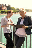 Two business women with tablet and smartphone working outside th Royalty Free Stock Photography