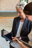 Two business women with tablets in a warehouse Stock Image