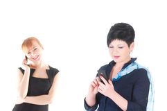 Two business women talking by cell phones Royalty Free Stock Images