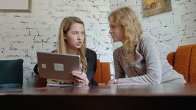 Two business women using a touchpad in the office are busy discussing matters. 4k stock footage