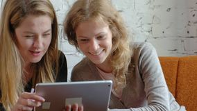Two business women using a touchpad in the office are busy discussing matters stock footage