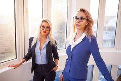 Two business women walking up on the stairs. In office building interior next to windows Royalty Free Stock Images
