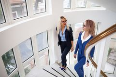 Two business women walking up on the stairs. In office building interior next to windows Royalty Free Stock Image