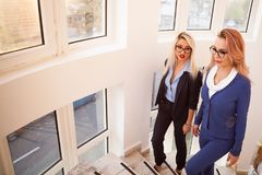 Two business women walking up on the stairs. In office building interior next to windows Stock Photos