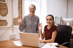 Two business women waving at camera Stock Photo