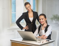 Two business women work at the laptop Stock Images