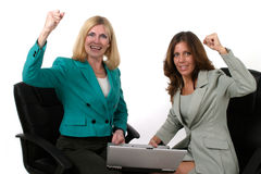 Two Business Women Working On Laptop 10. Attractive and beautiful two business woman team working at a laptop computer together.  Shot on white Stock Photos