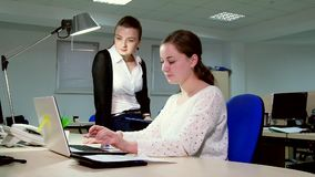 Two business women working in the office at the computer. Two business women working in the office at the computer stock video footage