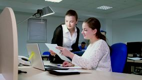 Two business women working in the office at the computer. Two business women working in the office at the computer stock footage