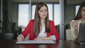 Two business women are working in the office. T. He girl in red jacket reads documents. The woman in the yellow jacket draws on the laptop screen stock video footage