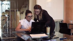 Two business women working in the office using a computer. Two beautiful business women working in the office using a mobile computer stock video