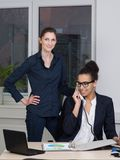 Two business women are working in the office. A young business women is phoning while sitting at the desk in front of a file. Another women is standing next to Stock Images