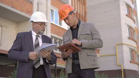 Two business worker in helmet discussing, using tablet near build. 4K.  stock video