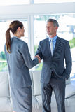 Two business workers shake hands Stock Photos
