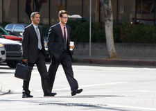 Two Businessman Chatting Whilst Crossing Street Royalty Free Stock Images