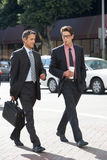 Two Businessman Chatting Whilst Crossing Street. Outdoors stock photography
