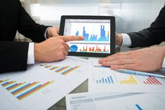 Two businessman discussing graph on digital tablet Stock Photos